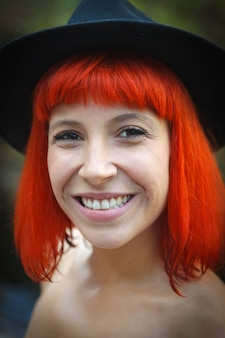 黒い帽子と服なしで自然の中で幸せなヒップスターの女の子