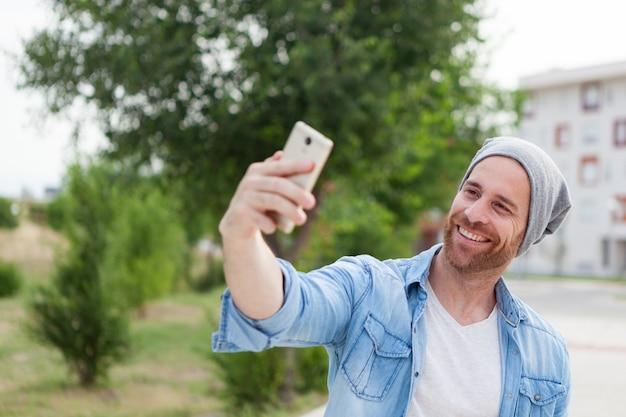 都市のモバイルで写真を撮っているカジュアルファッションの男