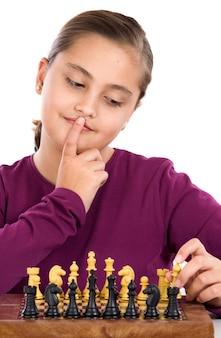 Привлекательная девочка играет в шахматы на белом фоне