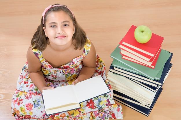 Очаровательная девушка со многими книгами, читающими на деревянном полу