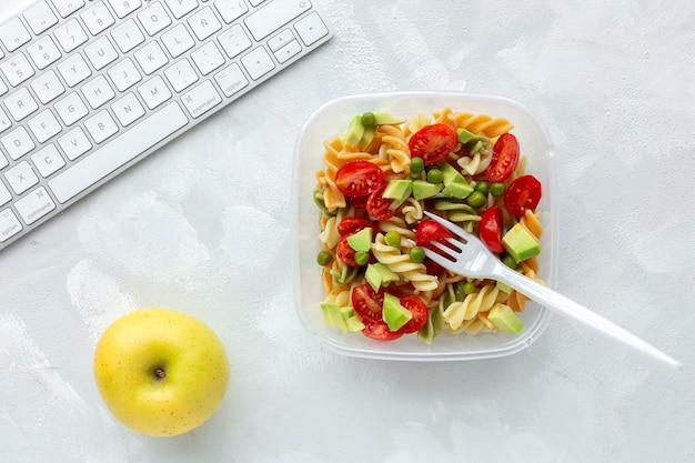 キーボード付きのオフィスの机の上の野菜とイタリアのパスタ