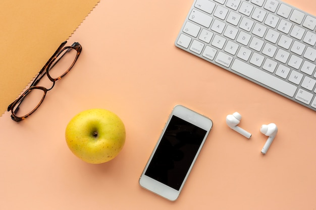 アップル、キーボード、イヤホン、スマートフォン、メガネを備えたワークスペース