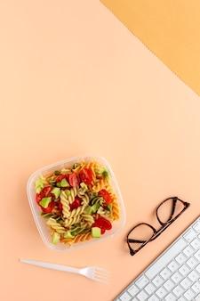 キーボードとメガネのオフィスデスクで野菜とイタリアンパスタ
