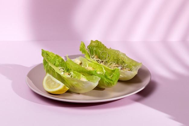Домашний салат цезарь с курицей, листьями салата, лимоном, тостами, цезарным соусом, сыром и чесноком