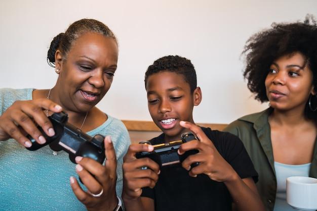 Ребенка учат бабушка и мама играть в видеоигры.