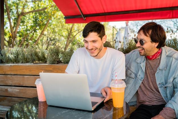 Два молодых друзей, используя ноутбук в кафе.
