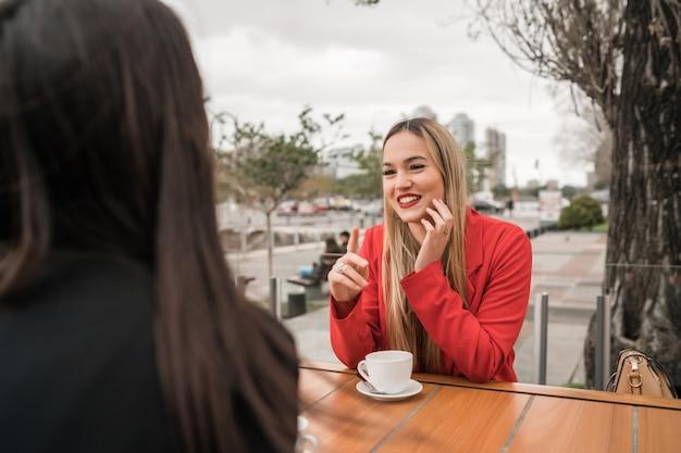 Две молодые друзья в кафе.