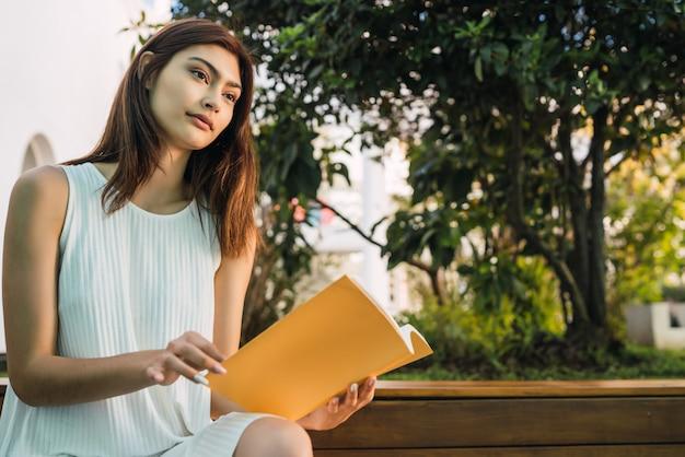 Молодая женщина читает книгу.