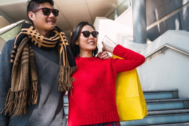 アジアのカップルがモールで買い物。
