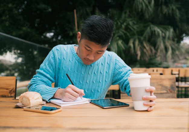 Азиатский человек учится в кафе.