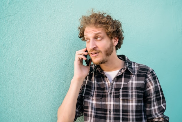 若い男が電話で話しています。