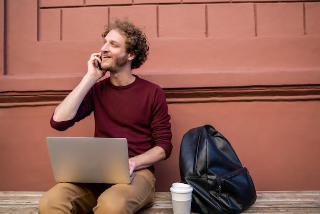 Молодой человек разговаривает по телефону.