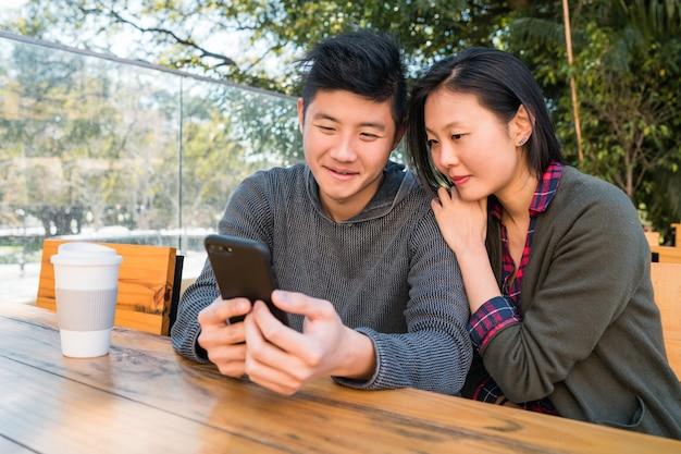 Азиатская пара, глядя на мобильный телефон.
