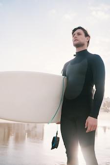 Серфер стоит в океане со своей доской для серфинга