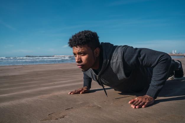 Спортивный человек делает отжимания на пляже