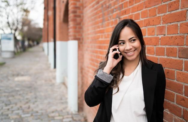 Латинская женщина разговаривает по телефону.