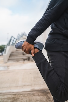 運動前に足を伸ばして運動の男。