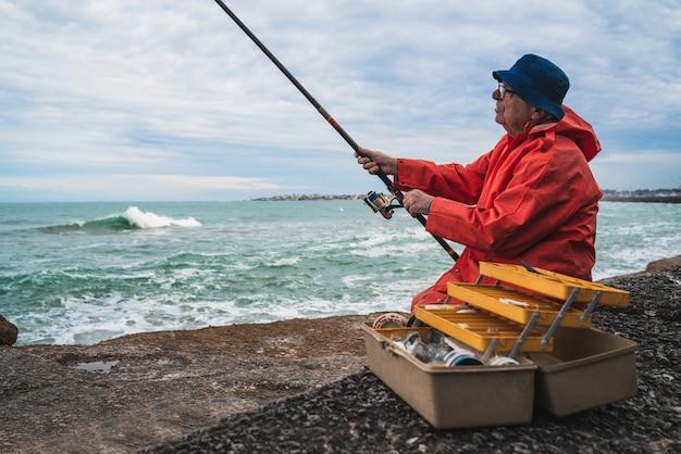 老人は海で釣り。