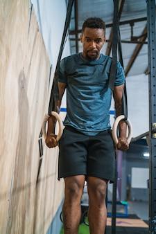リングで筋肉を鍛えている運動の男。