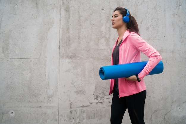 トレーニングマットを保持している運動の女性。
