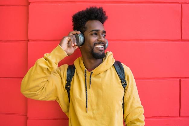 Молодой афро человек слушая музыку с наушниками.