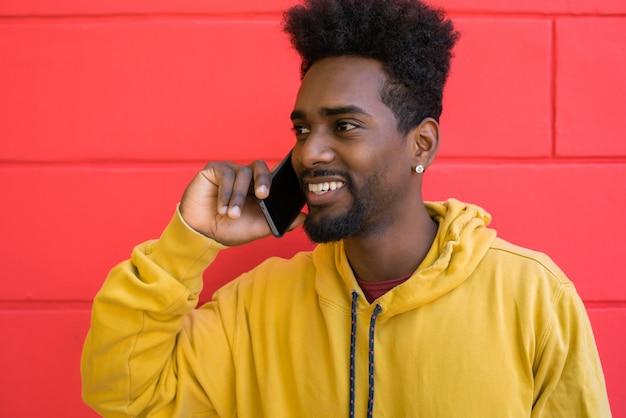 電話で話しているアフロ男。