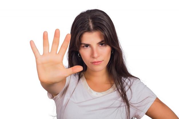 若い女性は彼女の手のひらで停止ジェスチャーを示します。