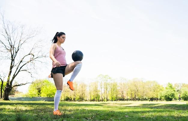 Портрет молодой женской подготовки футболиста и практикующих навыков на футбольном поле. спортивная концепция.