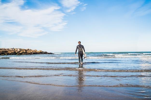 Молодой серфер, войдя в воду с его доски для серфинга в черном костюме для серфинга. спорт и водные виды спорта концепция.