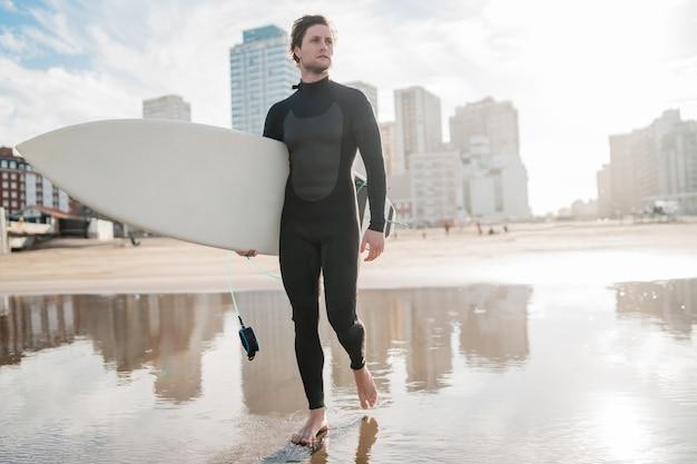 若いサーファーが彼のサーフボードを黒いサーフィンスーツで海に立っています。スポーツとウォータースポーツのコンセプトです。