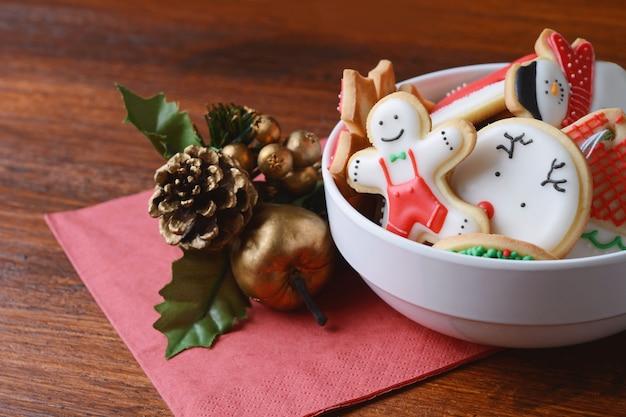 お祝いの装飾のボウルでカラフルなクリスマスのクッキー