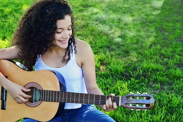 公園でギターを演奏する若い女性。