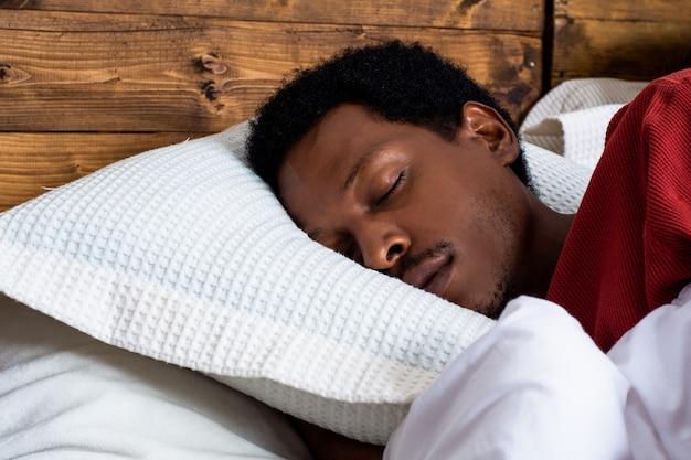 ベッドで寝ている若い男