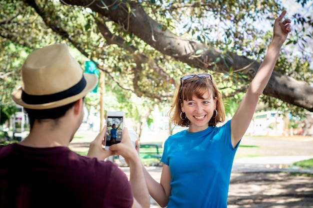 若いカップルがスマートフォンのカメラで写真を撮影します。
