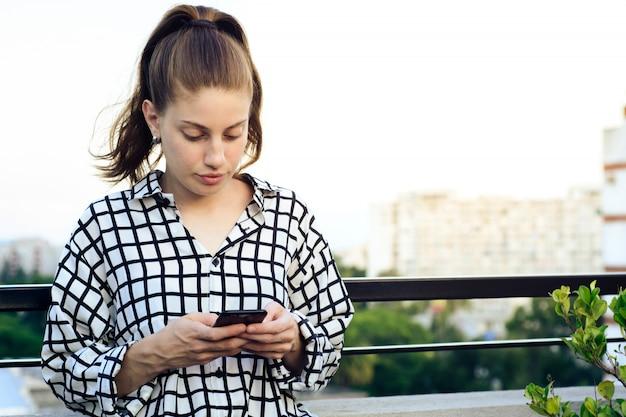 赤毛の女性がスマートフォンでメッセージを送信します。