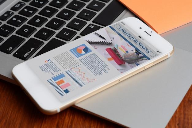 Смартфон со статистикой о росте компании