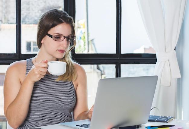 女性が自宅のラップトップに取り組んでいます。