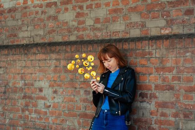 絵文字を送信するスマートフォンを使用しての女性。