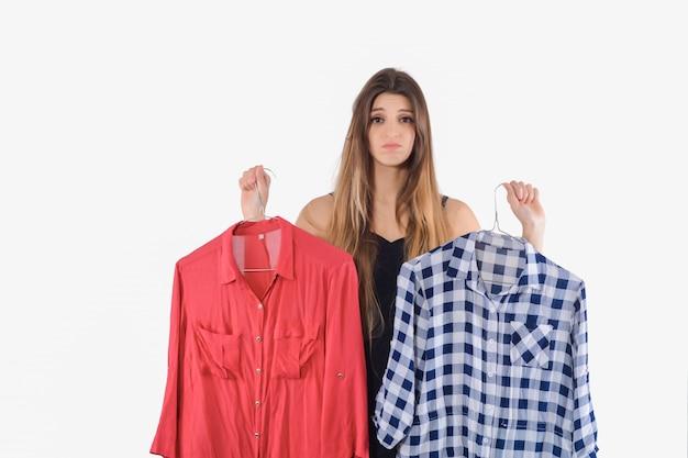 どの服を着るかを選ぶ女性。