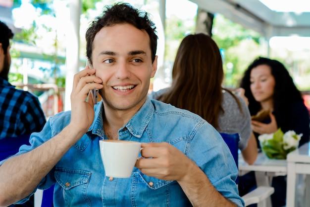 携帯電話を使用してコーヒーを飲む人