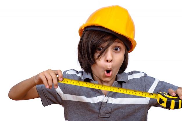 Маленький мальчик с шлемом и проведение измерительной ленты.