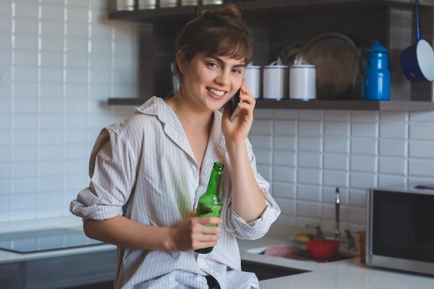 携帯電話で話している女性とビールを飲む