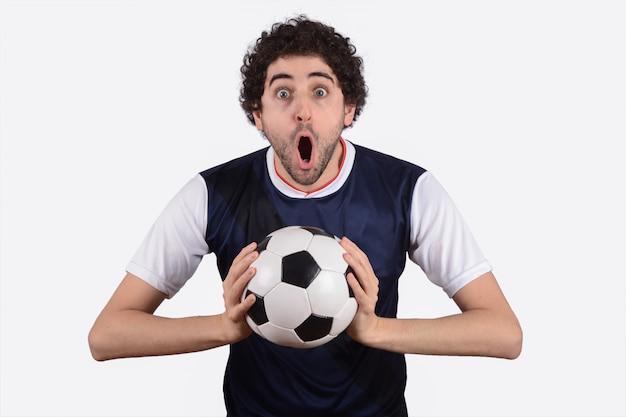 男はサッカーボールで叫んでいます。