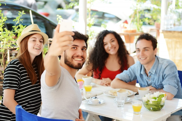 Группа друзей, принимающих селфи в кафе