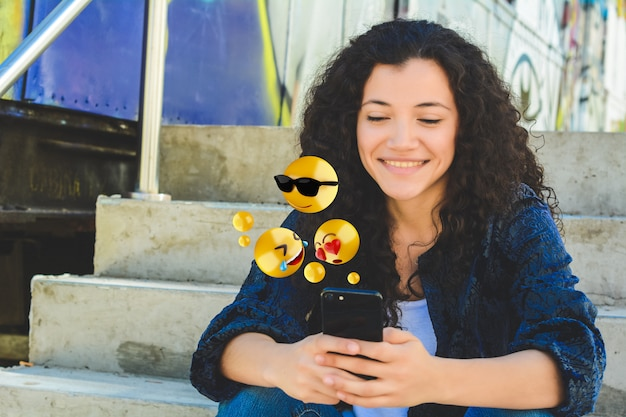 絵文字を送信するスマートフォンを使用しての女性