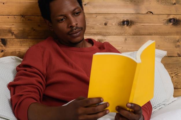 男はベッドに敷設し、本を読んで