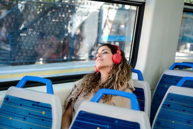 窓の横にある電車旅行で寝ている都市の女性。