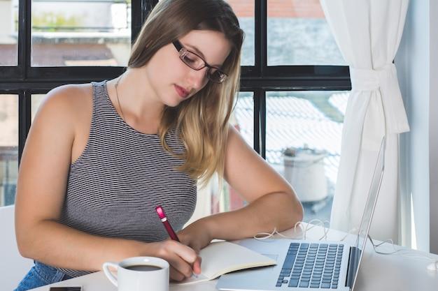 自宅のラップトップに取り組んでいる女性。