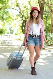 通りにスーツケースを運ぶ観光客女性