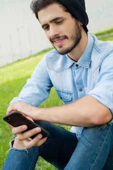 若い男が彼の電話を屋外で使う